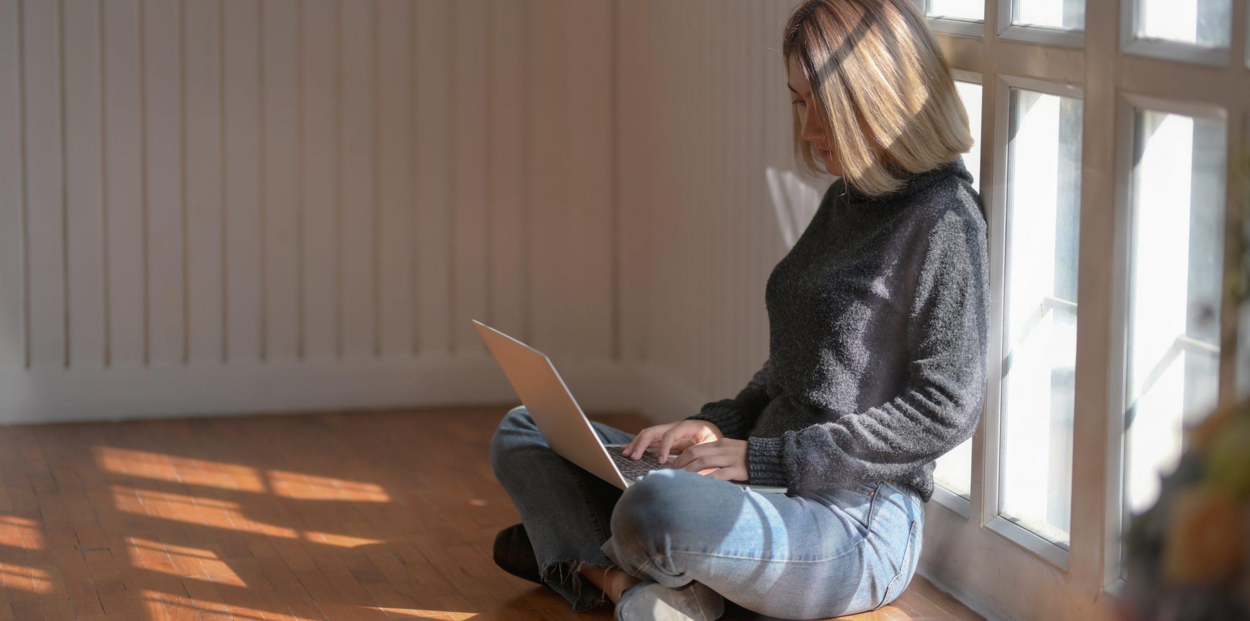 Κοπέλα κάθεται στο πάτωμα μαζί με το λαπτοπ της